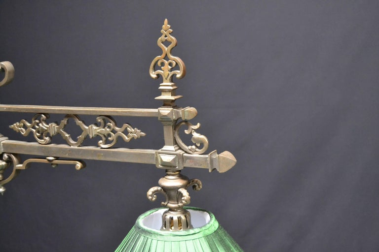 A superb decorative cast brass framed Billiard , snooker or pool table lamp featuring a central horizontal framed frieze with ornamental castings , joined to a central upright via embellished cast braces, adorned with a cast symbol of