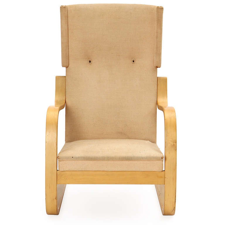 A rare and sculptural wingback lounge chair having a cantilevered laminated birch frame and retaining its original handstitched textured linen upholstery.
