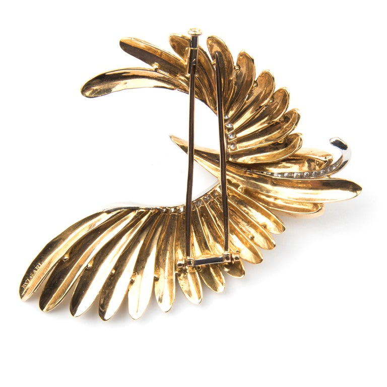 Bulgari brooch in the shape of a flying bird with feathers in 18k yellow gold, the stylised body platinum set with brilliant cut diamonds. Probably unique. Signed Bulgari Circa 1970 In original box