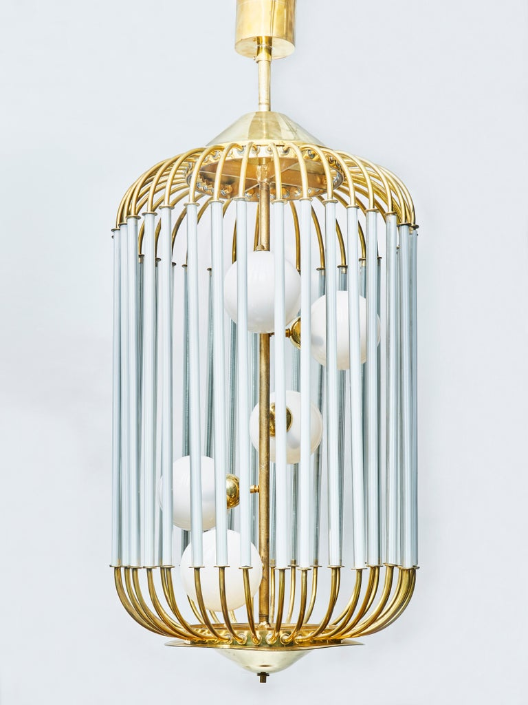 Particularly original chandelier shaped like a bird cage, tinted glass sleeves around the bars circling around a central stem holding five-light in white glass globes.