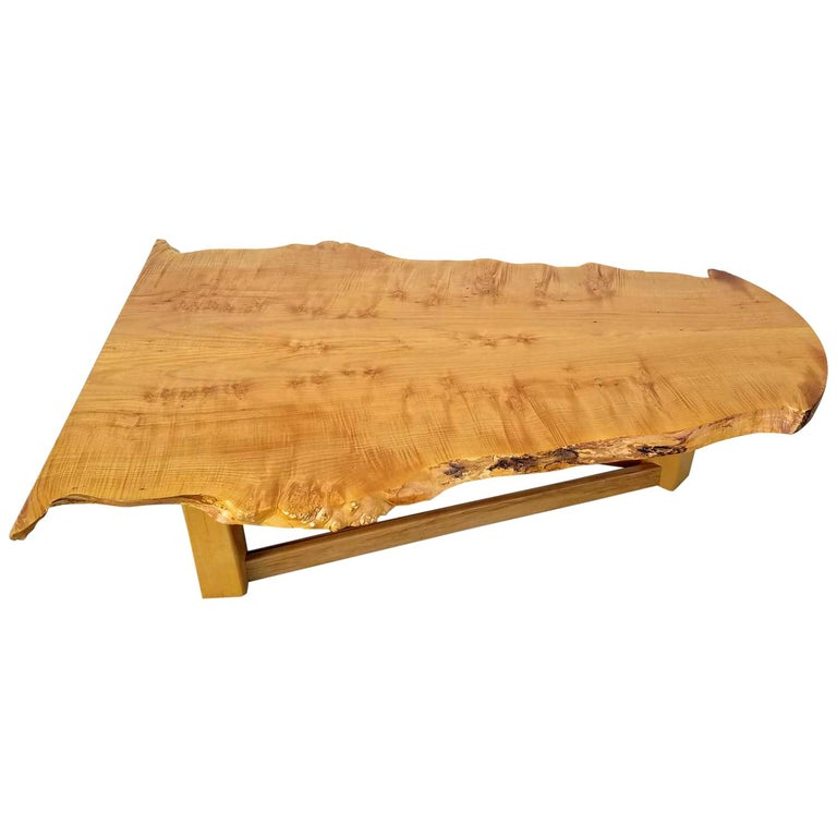 Exceptional bird's-eye maple slab coffee table with natural live edge. This table caught our eye for it's distinctly modern spin on they typical rustic slab. Notice how the top surface has been expertly milled to have a perfect plane. The millwork