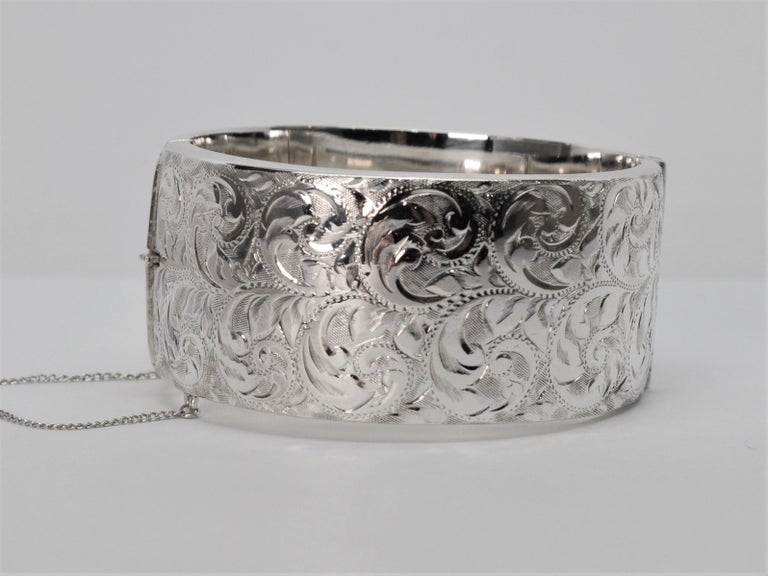 For vintage silver lovers by CPS Jewelry Company, Birmingham, England, this highly polished 1-1/4 inch wide sterling bangle bracelet boldly presents a decorative hand engraved pattern design on it's face and a smoothly finished back.  To determine