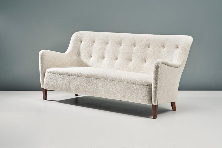 This exceptional piece of Danish furniture was designed in the 1940s by designer Birte Iversen and produced by master cabinetmaker A.J. Iversen. This example has been reupholstered in luxurious cotton-wool blend boucle fabric from Dedar Milan at our