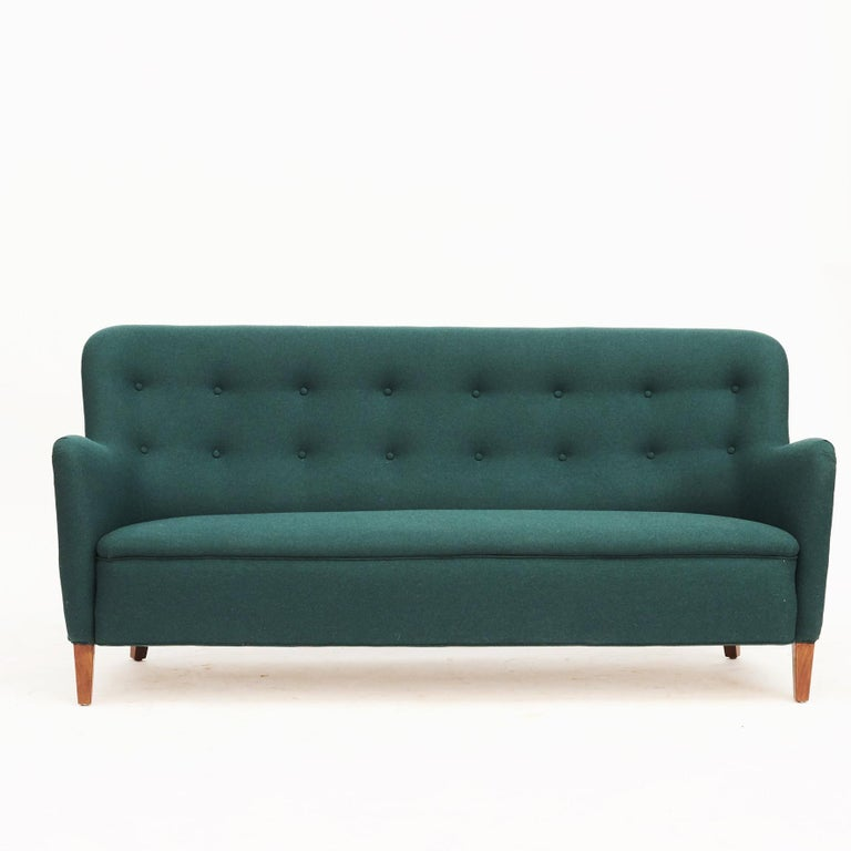 A living room set including a three-seat freestanding sofa and two easy chairs. Designed by Birte Iversen, Denmark, circa 1940-1950. Cabinetmaker A.J. Iversen, Denmark. Newly upholstered with wool in deep green from Nobilis.  Sold as a set (3