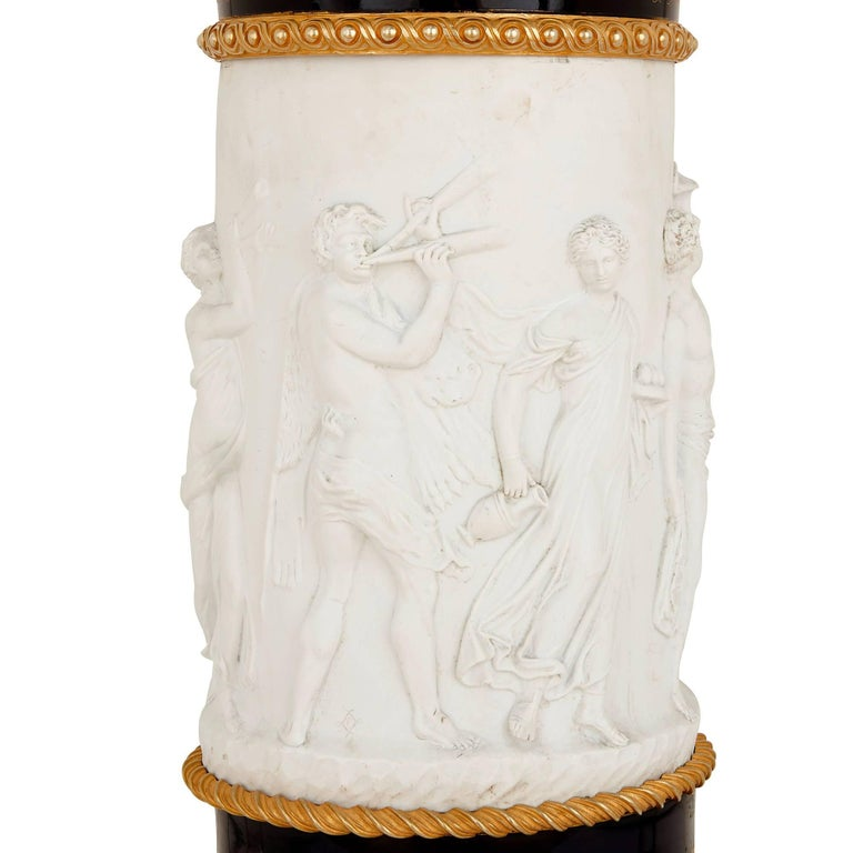 This unique pedestal is crafted from a combination of glazed and unglazed porcelain, mounted elegantly with gilt bronze. The unglazed porcelain - known as biscuit (or bisque) porcelain - is white in colour and has a matte finish, contrasting
