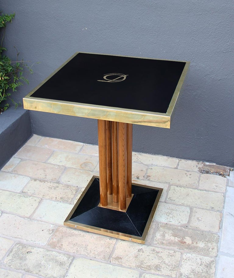 Very beautiful bistro (bistrot) table coming from the French restaurant, Drouant. This square table is composed of a black glass framed in brass and mounted on a black base, which is also framed in brass. The glass features a gilt logo. The top and