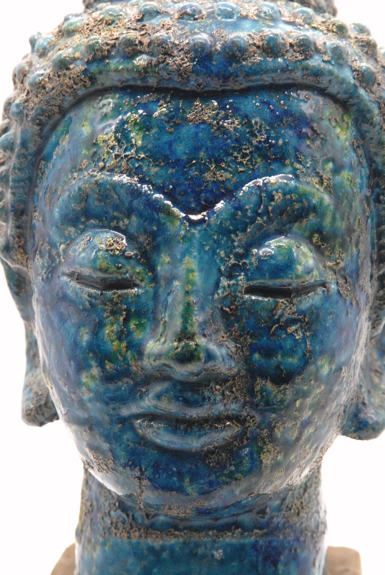 A stunning Aldo Londi designed Buddha head in the 'Cinese' [Chinese] glaze, replicating ancient bronze pieces that have been on the ocean floor for millennia. The glaze is fragile and this piece is in excellent order.