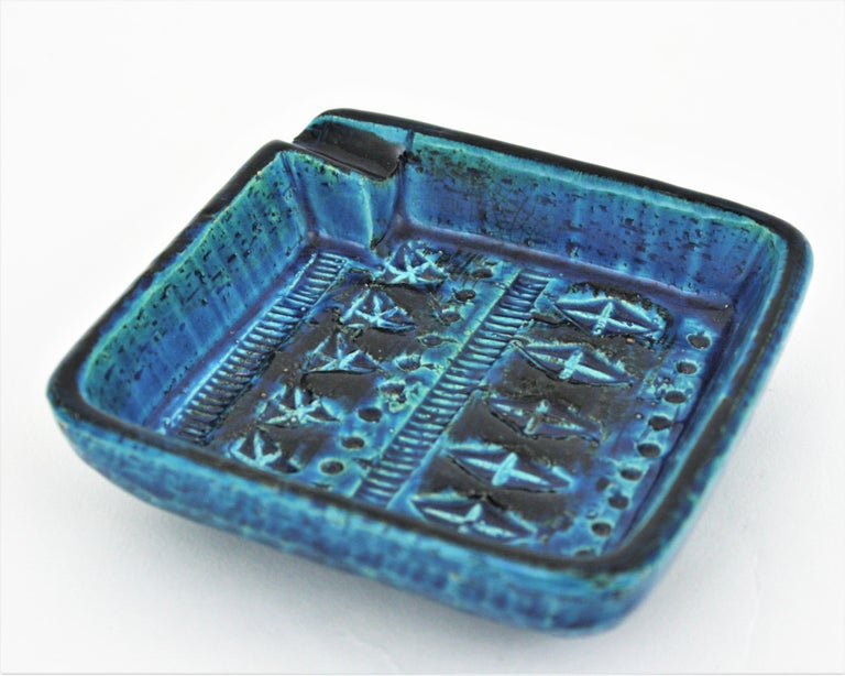 Small 'Rimini blu', blue glazed terracotta ceramic squared ashtray. Design by Aldo Londi and manufactured by Bitossi. Italy, 1950s-1960s. Handcrafted in Italy with hand carved geometric design and in a glazed vibrant turquoise and cobalt blue.  It