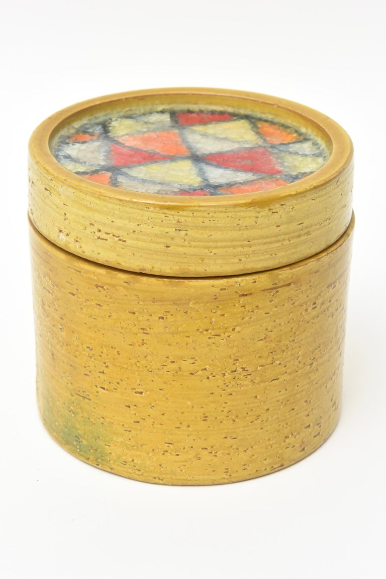 This lovely vintage Bitossi for Raymor glazed ceramic round lidded box is from the 1960s and is Italian. It has the fused glass mosaic insert on the top. The rich color of the mustard yellow exterior plays well with the multicolored broken fused