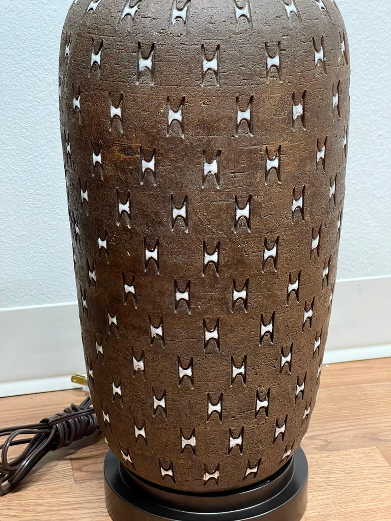A large pottery lamp by Bitossi. Great pattern and coloring. Signed on the base made in Italy. The base we had remade and painted brown while the wiring is new as well. The pottery has some inherent glaze flaws and imperfections. Pottery itself is 1