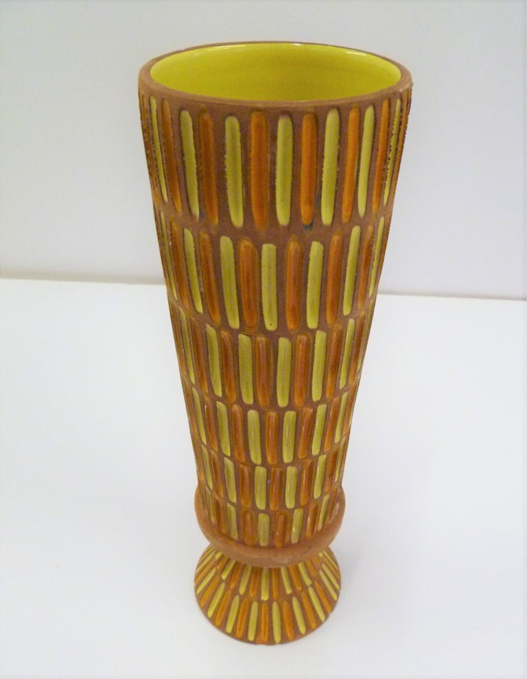 A tall Italian Mid-Century Modern footed Pottery vase produced by Bitossi in the 1960s for retailer Raymor and designed by Aldo Londi. This vase features an unglazed clay body with glazed incisions colored in bright orange and lemon yellow and lemon