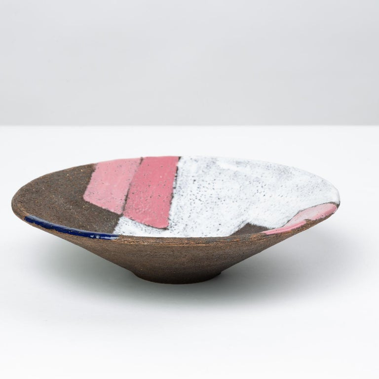 A decorative bowl with straight-slanted sides from Italian ceramicist Bitossi. Attributed to Aldo Londi, this patchwork design from the 1960s employs thin washes of hand-painted glaze to a textured stoneware surface, creating a patchwork effect of
