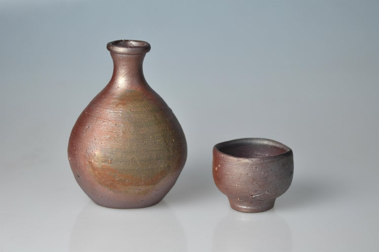 This set of a Bizen sake flask and cup was made by Fujiwara Yu who was born 1932 in Honami in Bizen, Okayama prefecture. As son of famous Fujiwara Kei (1899-1983) he has also been awarded the title