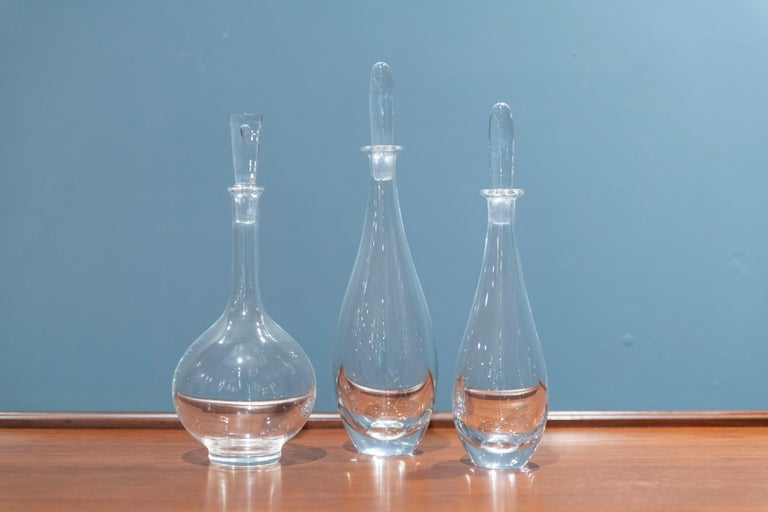 Pair of Orrefors decanters designed by Bjorn Wiinblad and a single Steuben glass decanter, all signed.