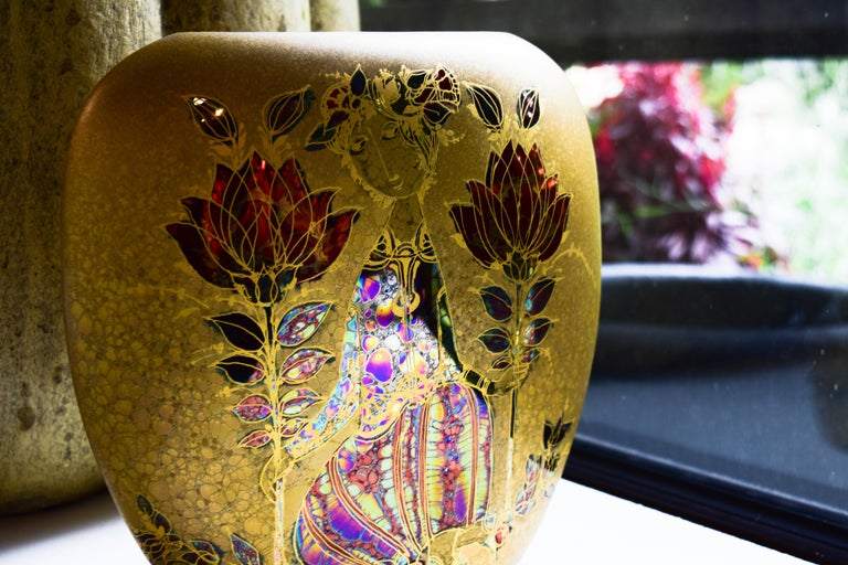 This vase is one example of the captivating style brought to life by the whimsical mind of artist Bjorn Wiinblad. Delightfully colored in metallics and 24-karat gold, the vase features the trademark round faces and complex detail that made Wiinblad