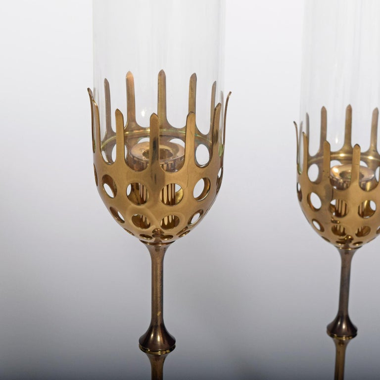 Bjørn Wiinblad: Two hurricane brass candlesticks with cylindrical clear glass shades. Marked monogram Bjørn Wiinblad, made in Denmark.