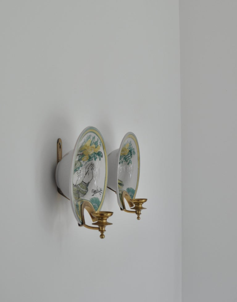 Faience wall plaques decorated in polychrome colors. Unique artworks made by Bjørn Wiinblad in his own studio in 1976. The pieces are made in the style of old shaving dishes and the brass mounts can also be used as candleholders. Great condition.