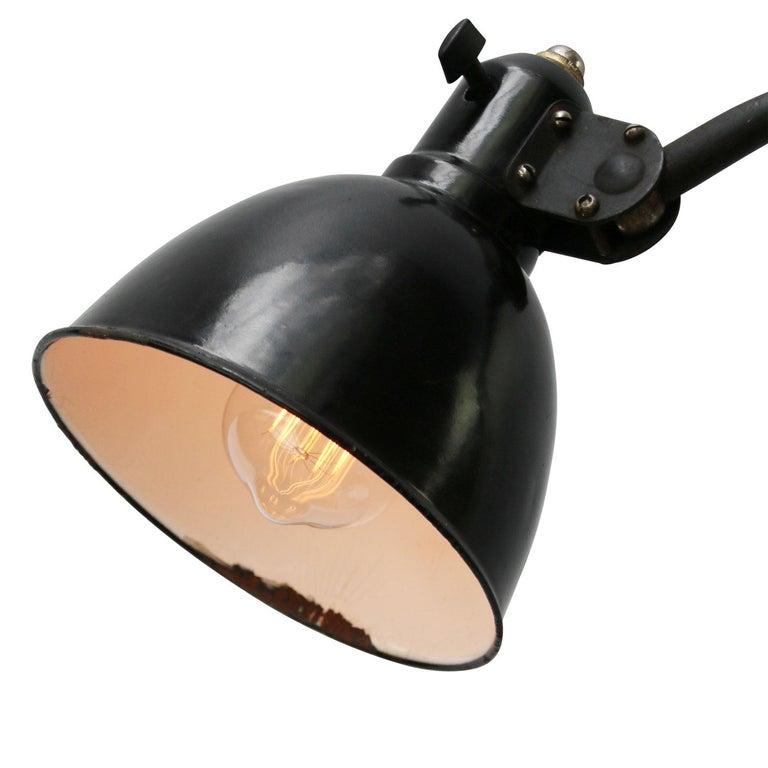 Black enamel industrial 2 arm work light by Peter Behrens for AEG, circa 1920s adjustable in height and angle including plug and switch  Weight: 2.40 kg / 5.3 lb  Priced per individual item. All lamps have been made suitable by international