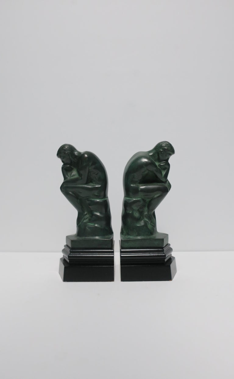 A great pair of 'Thinker' male figurative sculpture bookends in dark green with black bases, circa late 20th century. Each measuring 9.25
