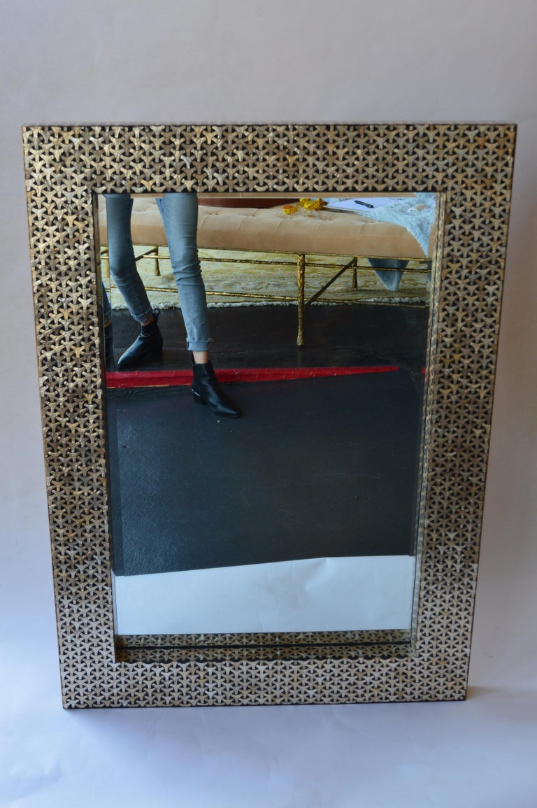 Mirror with geometric mother of pearl design set in a black frame. The mirror can be hung both vertically and horizontally.