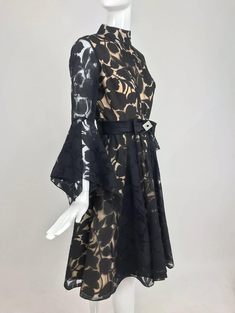 Black and nude voided organza handkerchief sleeve dress from the early 1960s...Dressmaker made this beautiful cocktail dress features a banded collar, fitted bodice and long sleeves with dramatic handkerchief cuffs...Seamed waist with a flared skirt