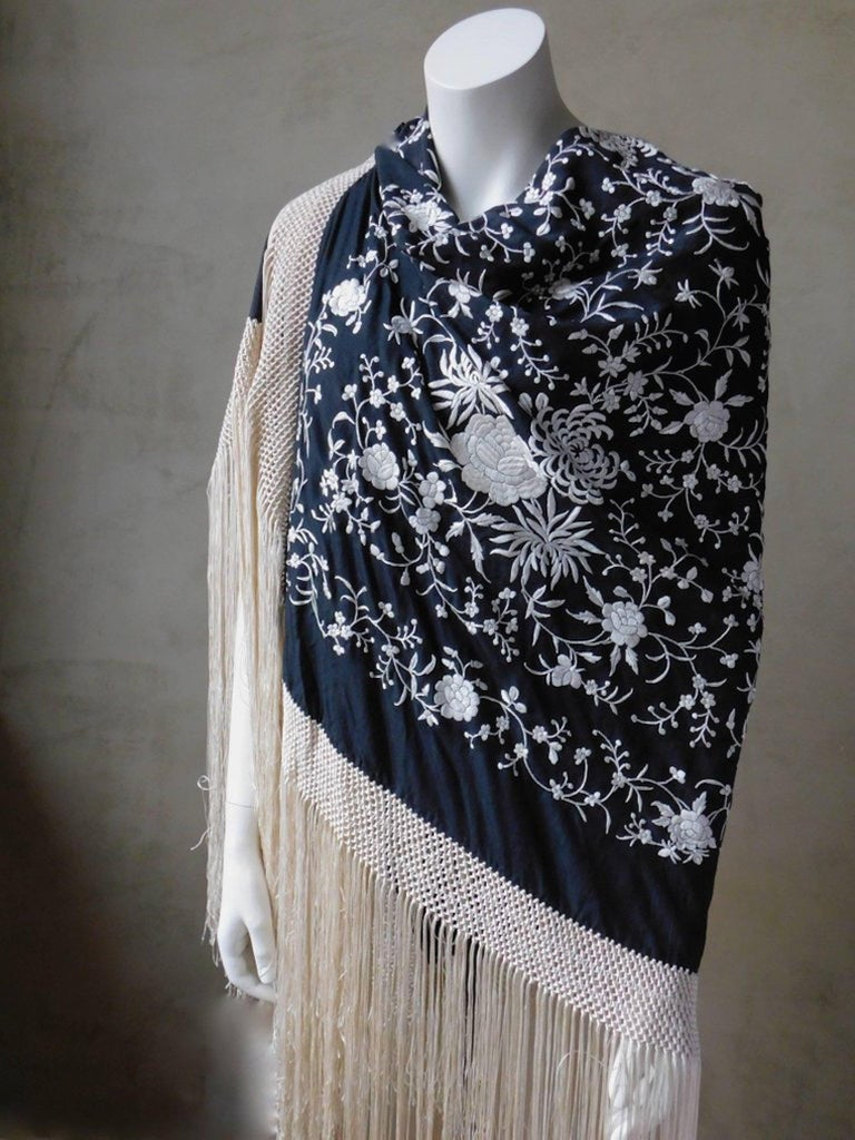 Stunningly elegant black and white Cantonese embroidered silk piano shawl. Black silk heavily hand embroidered with white silk thread and completely finished all around with long macrame tied white very long silk fringe. In excellent