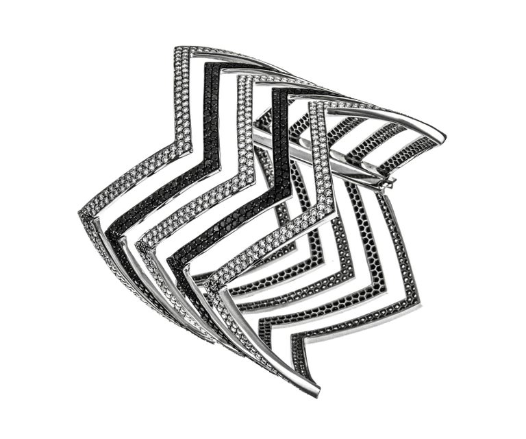 Constrasting black and white diamonds are the theme of this elegant and timeless cuff. The chevron design is delicately carved out of 18k white gold giving the piece a modern edge. Over 17 carats of alternating black and white diamonds are pave'd