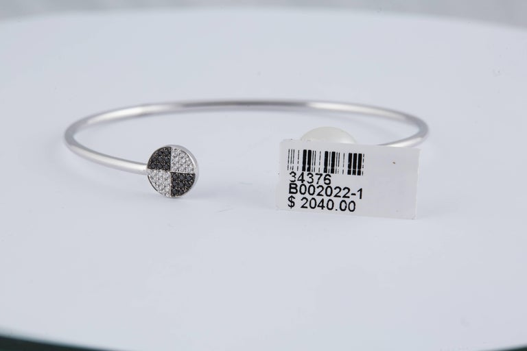 18K White gold bangle bracelet featuring 16 Black diamonds, 0.06 carats, 16 White diamonds, 0.06 carats, and one South Sea Pearl measuring 11 MM.