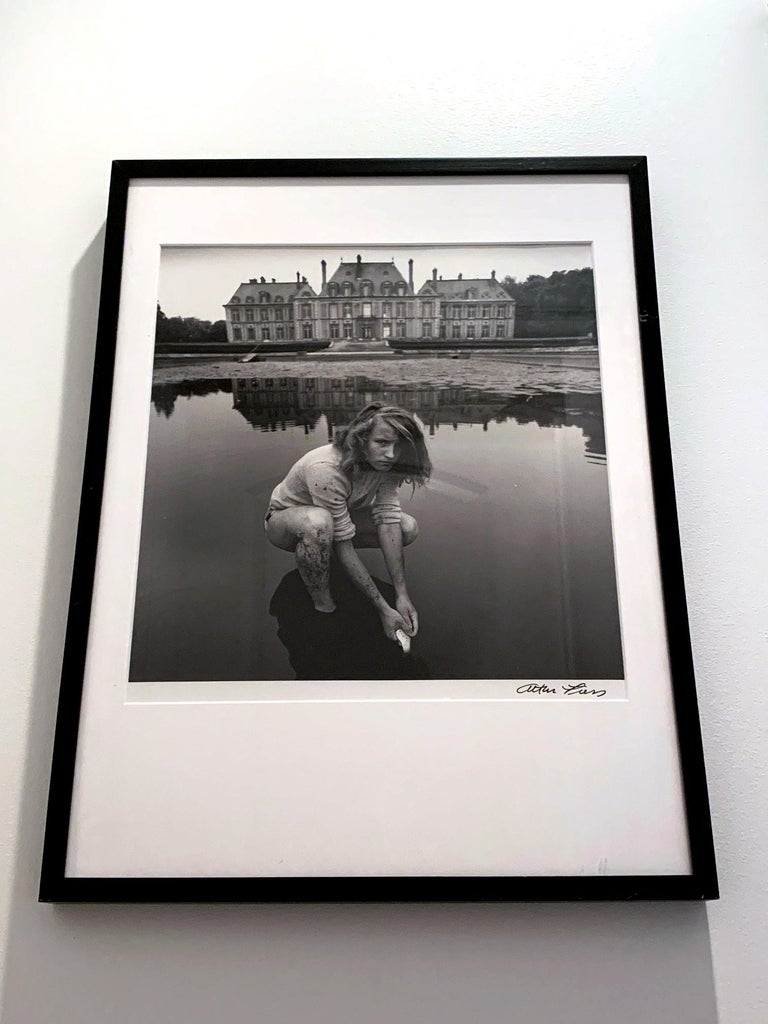 A large black and white photograph by American surrealist photographer Arthur Tress (born 1940-). The photo was entitled: Girl Collecting Goldfish, Chateau Breteuil, France. It was created in 1974 and it is not known when the photo on offer was