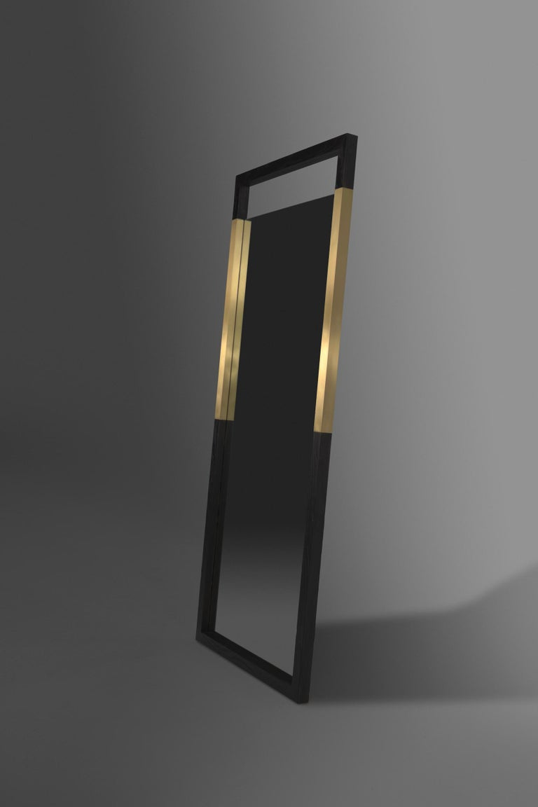 The Broadway standing mirror is a modern mirror made of charred ash wood and brass metal inserts. The open space at the top and bottom add to the modern look of the mirror and allows for the brass to be emphasized even more. This item can also be