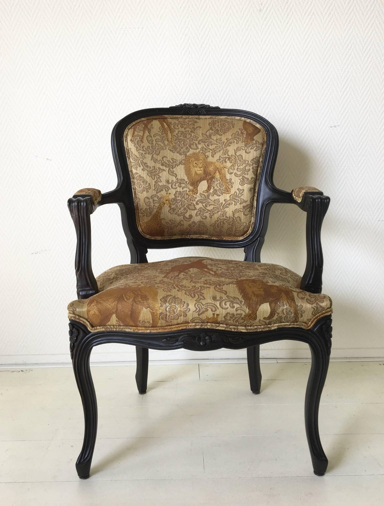 Exclusive design by the Spanish family company Ascension Latorre. The company is known for their hand made furniture. The chair features an ebonized wooden base with a gold colored upholstery with wildlife animals. This extraordinary piece remains