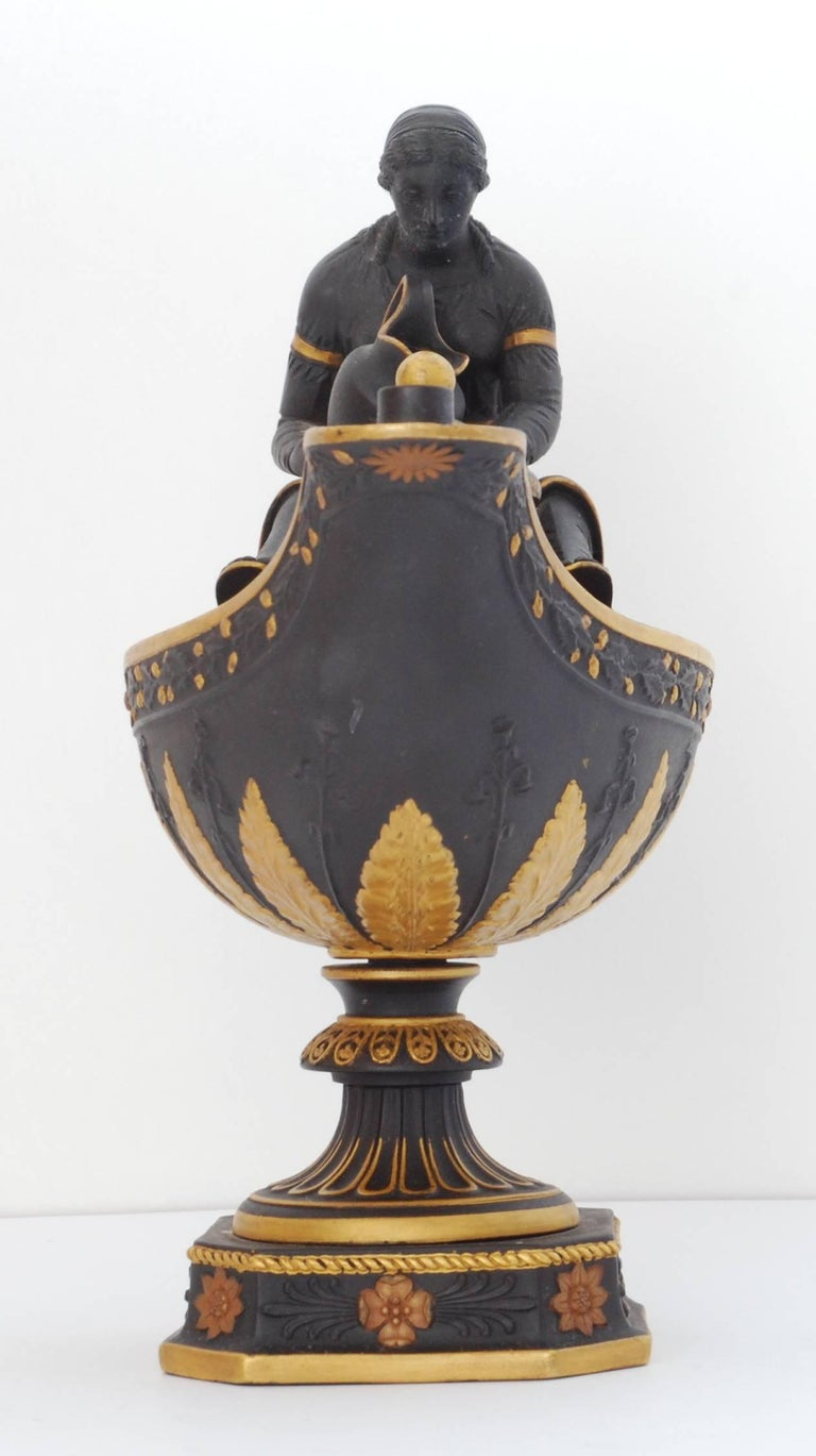 An oil lamp in basalt with rare gilt and bronze highlights. The presence of a 'sump cover' shows that this is an early example, intended to be used.