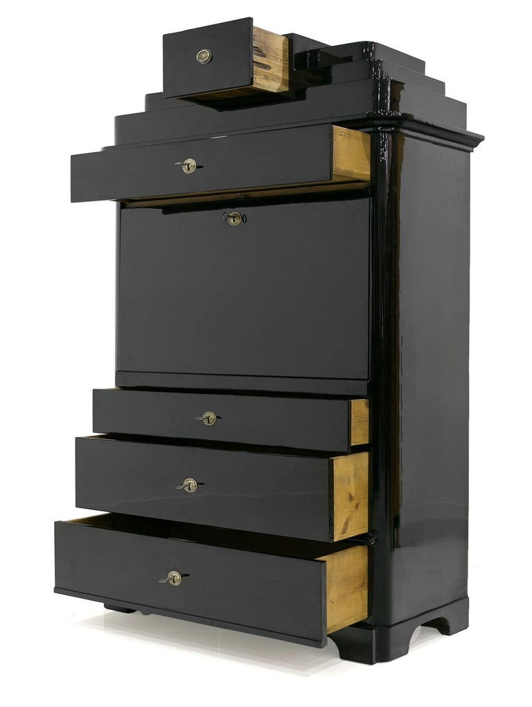 This is a beautiful Secretary from the Biedermeier era. It is made of walnut wood finished in black polished to high gloss. The interior of the furniture is kept in natural wood colors which creates a nice contrast and gives it an elegant look. The