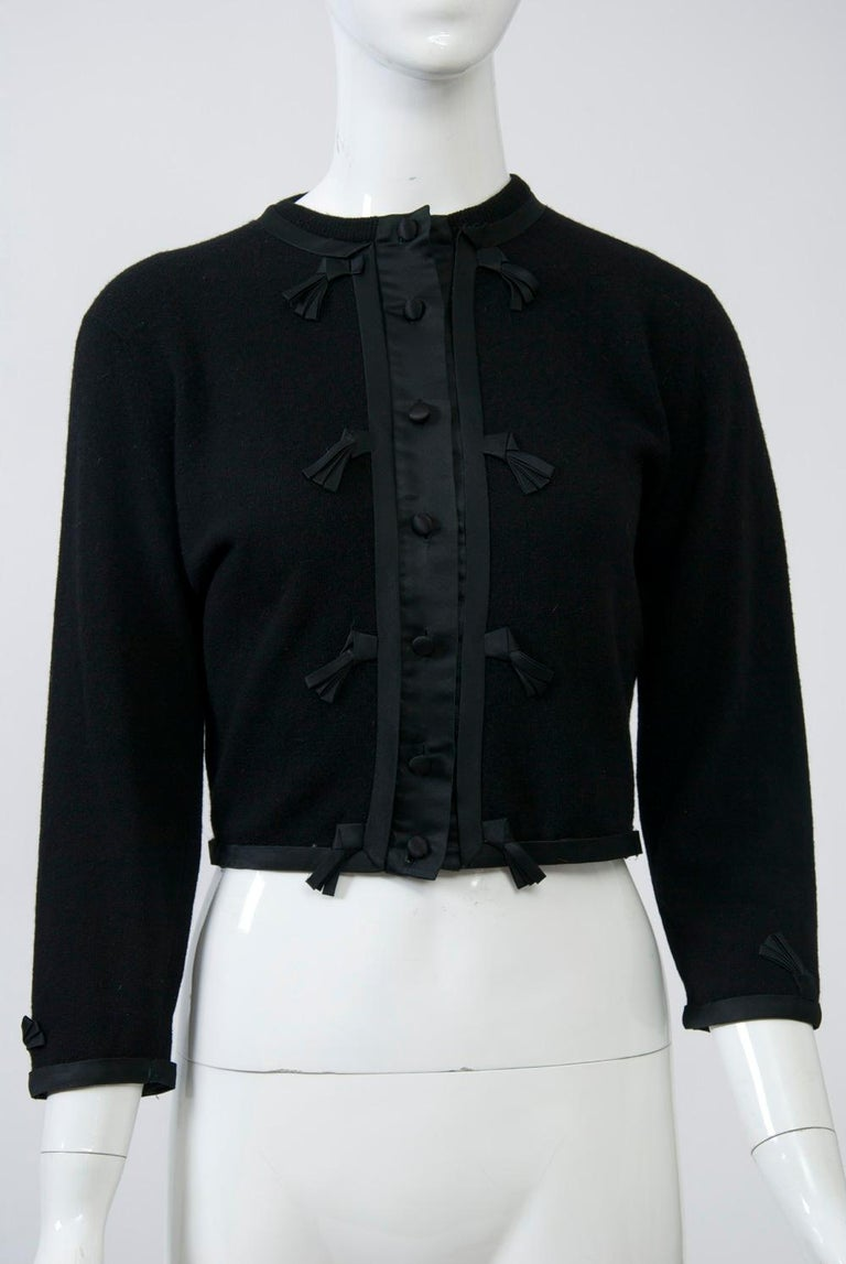 Cropped vintage cardigan in black cashmere featuring black satin trim further adorned with small fringe detail. Matching satin buttons. Unlined. A lovely example of the embellished cardigans popular during the 1950s and '60s. Petite/small size.