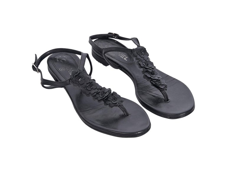 Product details:  Black leather thong sandals by Chanel.  Adjustable ankle strap.  T-strap accented with camellia floral applique.  Silvertone hardware.   Condition: Pre-owned. Very good. Est. Retail $ 995.00