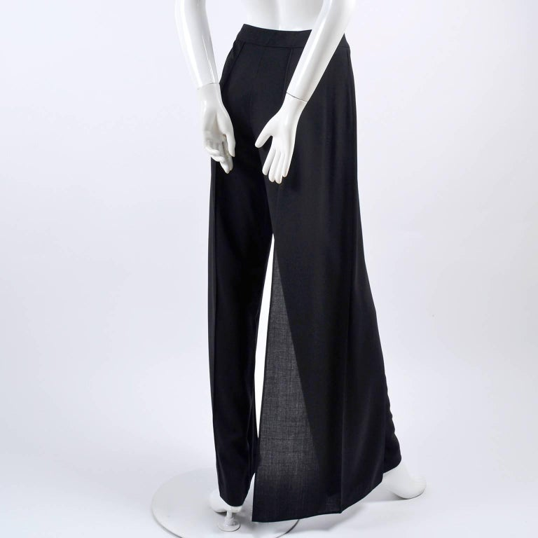 These black Chanel Pants are new with their original tags attached. The high waist pants are from spring 1999 and are made of black 100% ultra fine wool. The fly away panel on one of the sides give the appearance of palazzo style pants, as well as