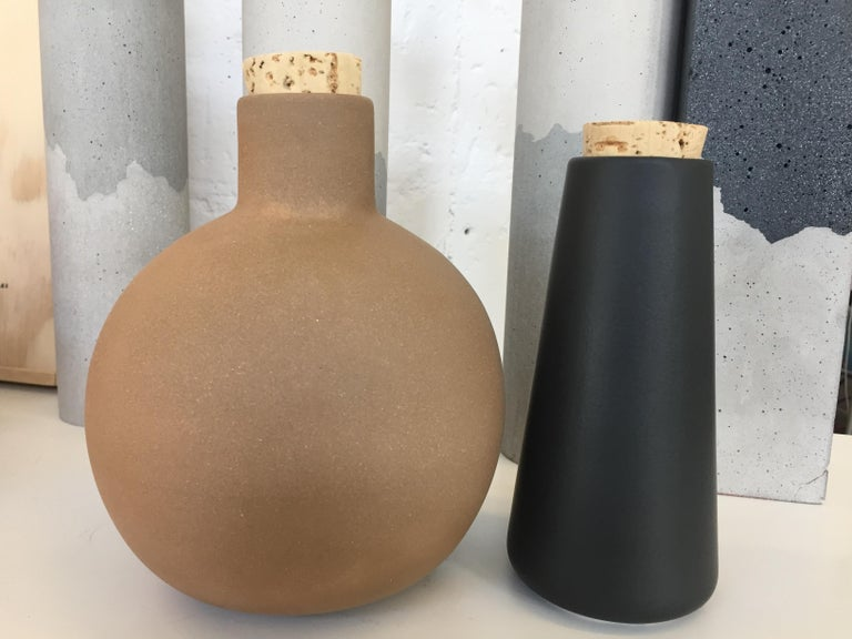 High fire black clay with cork lid. Handmade by artisans in Ciudad de Mexico. Perfect to store oil, vinegar or your favorite tequila.  10 oz.  Size: Ø 3