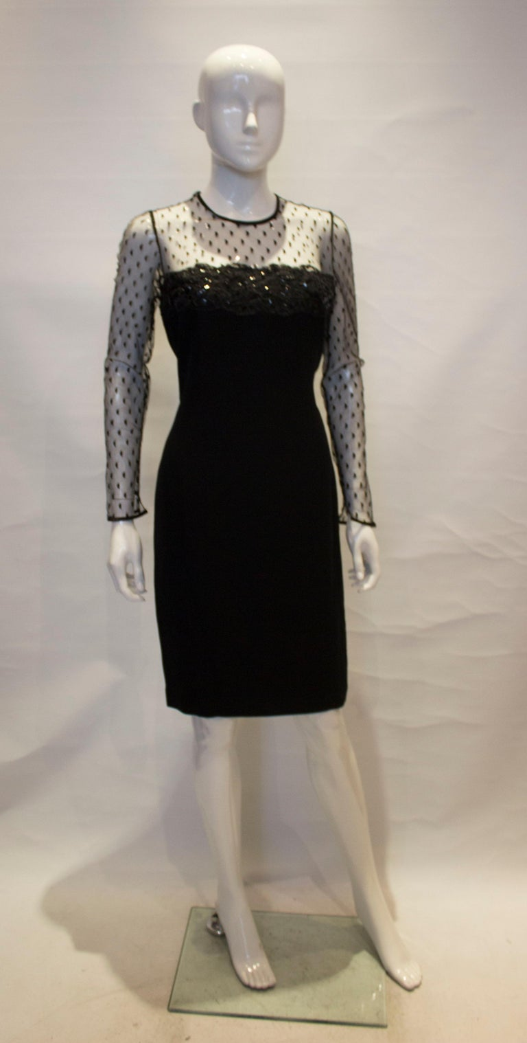 A chic black cocktail dress by Adrienne Vittadini. The dress has net sleaves and upper area front and back . It is fully lined, with a central back zip and 5 1/2 '' slit at the back.