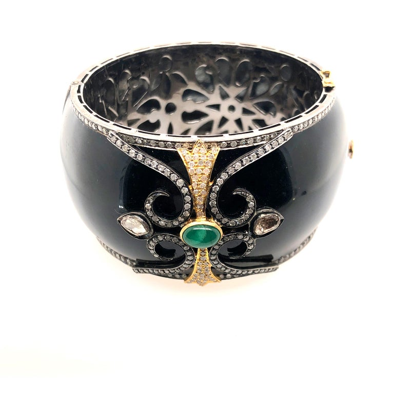 Designer black enamel bangle with diamond motif on top and around. This bangle is openable and has beautiful floral silver grill inside for smooth feel inside.  Closure: Box Clasp  14k: 5.74gms Diamond: 5.1ct Silver: 92.4gm Emerald: 1.5ct
