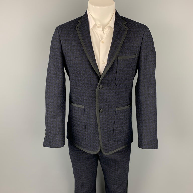 BLACK FLEECE tuxedo suit comes in a black & navy houndstooth wool with a grosgrain trim and includes a single breasted, three button sport coat with a notch lapel and matching flat front trousers. Made in USA.  Very Good Pre-Owned Condition. Marked: