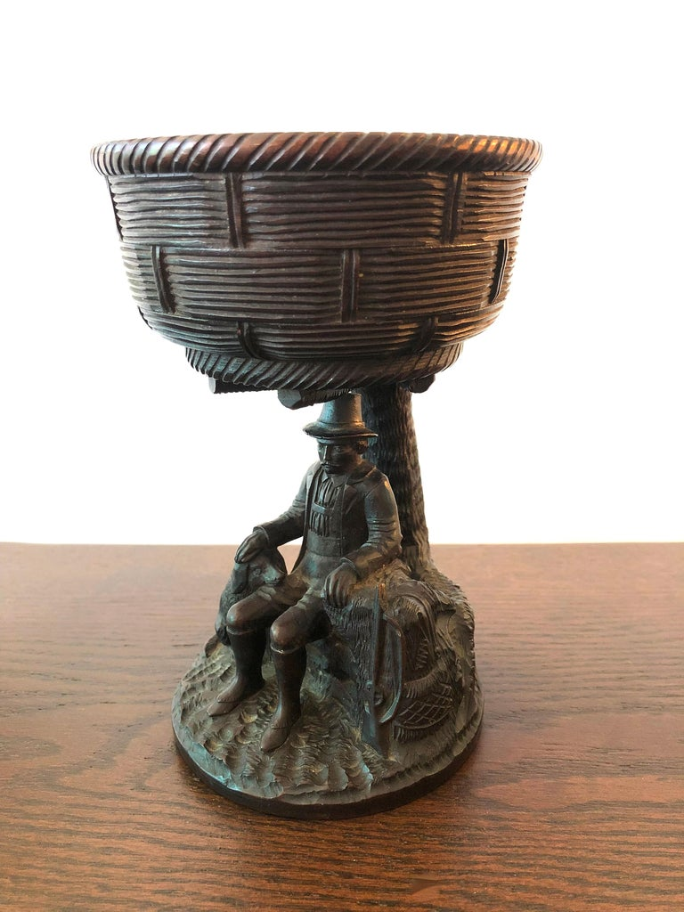 A beautifully crafted Black Forest hand carved walnut hunting presentation cup, the basket weave bowl supported by the figure of a gentleman hunter leaning against a tree trunk with his gun at one side and his hand on the head of his faithful dog
