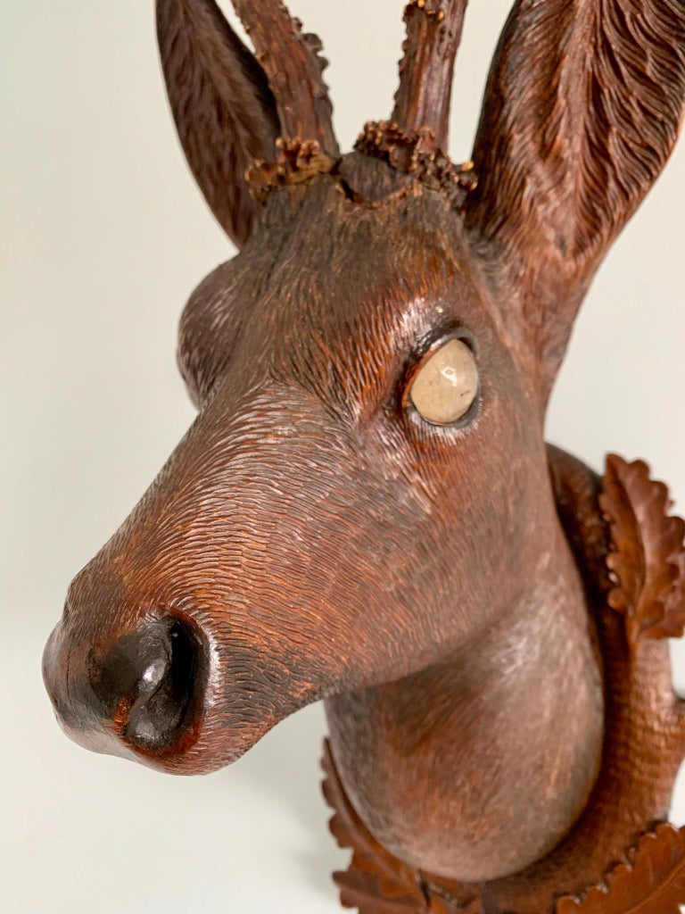 Hand carved Bavarian wood Deer head with real antlers on plaque. The execution is excellent with fur tinted to imitate natural coloring. The eyes are glass. The plaque is carved with oak leaves.
