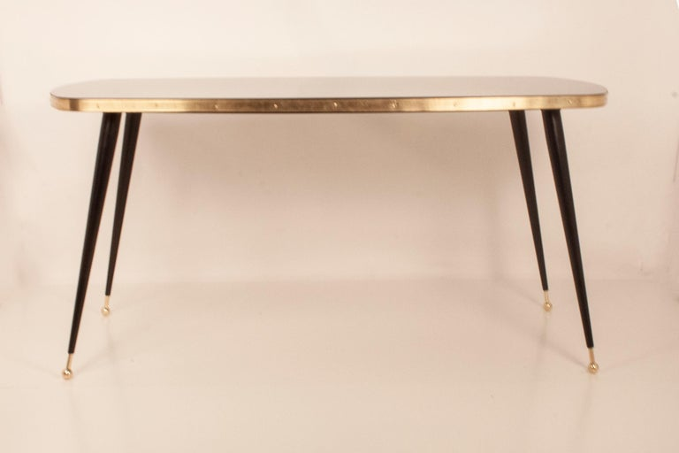 Black glass dining table, brass, black iron legs, Spain. New Dining table made in DM and with white glass top. The iron legs are lacquered in black. Golden brass leg termination. It can be done in different; shapes (round, square, oval ....) back