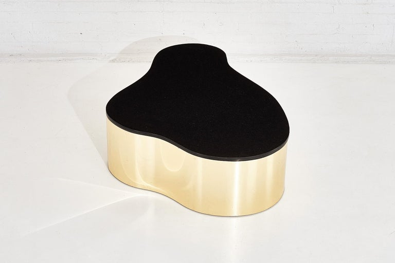 Black granite and brass biomorphic coffee table in style of Karl Springer, circa 1980s.