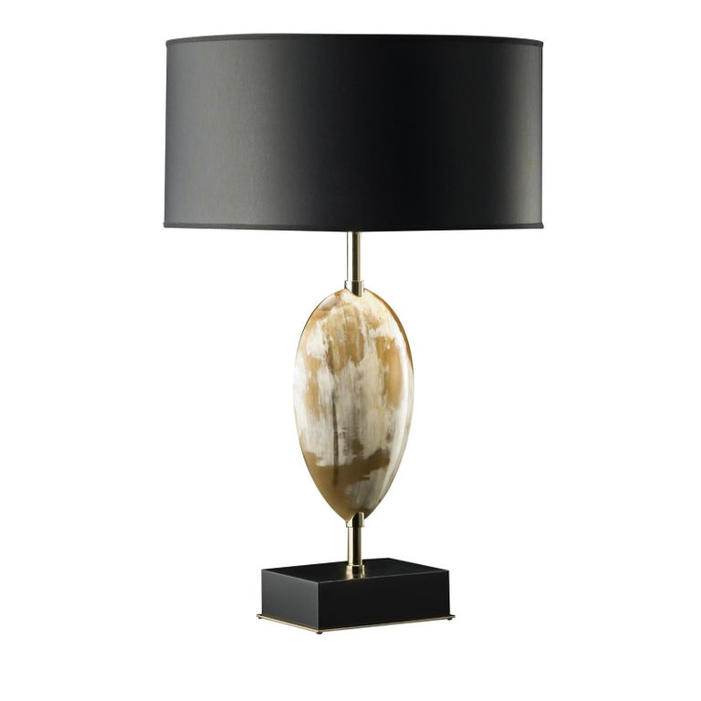 This unique table lamp is a prime example of impeccable artistry that will imbue elegance to any decor with its modern heirloom quality. The square wood base, raised on 24-karat gold-plated brass platform, with a lacquered black gloss finish, acts