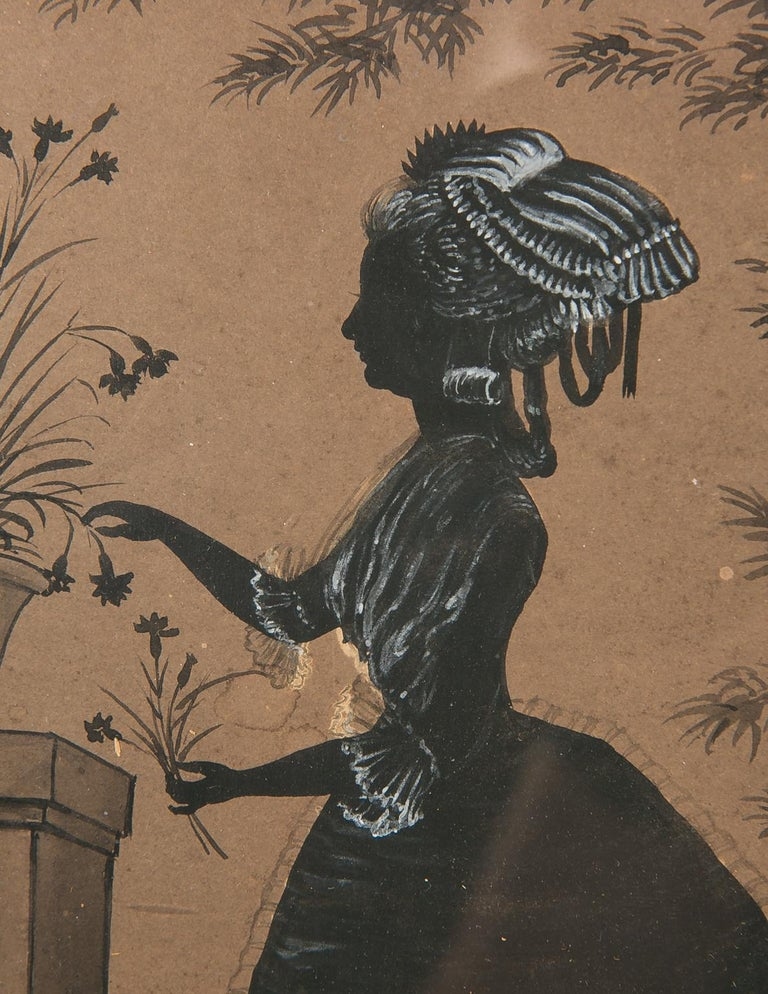 We are pleased to offer this lovely English painted silhouette of a young lady arranging flowers. The scene is drawn in black ink with delicate white gouache details for the lace on the woman's hair, hat and garments. In painting the silhouette, the