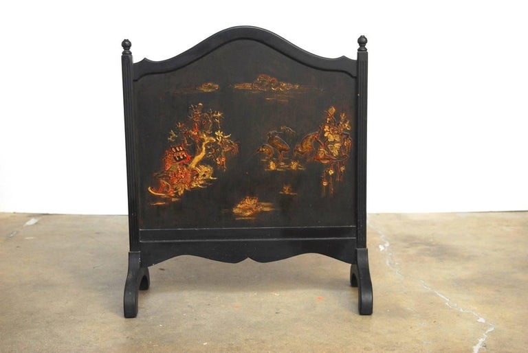 Continental black lacquer fireplace screen decorated in the chinoiserie taste. Features scenes with pagodas and cranes under clouds. Painted in the Japanese moriage style with raised images. The arched crest has a finial on each end and the screen