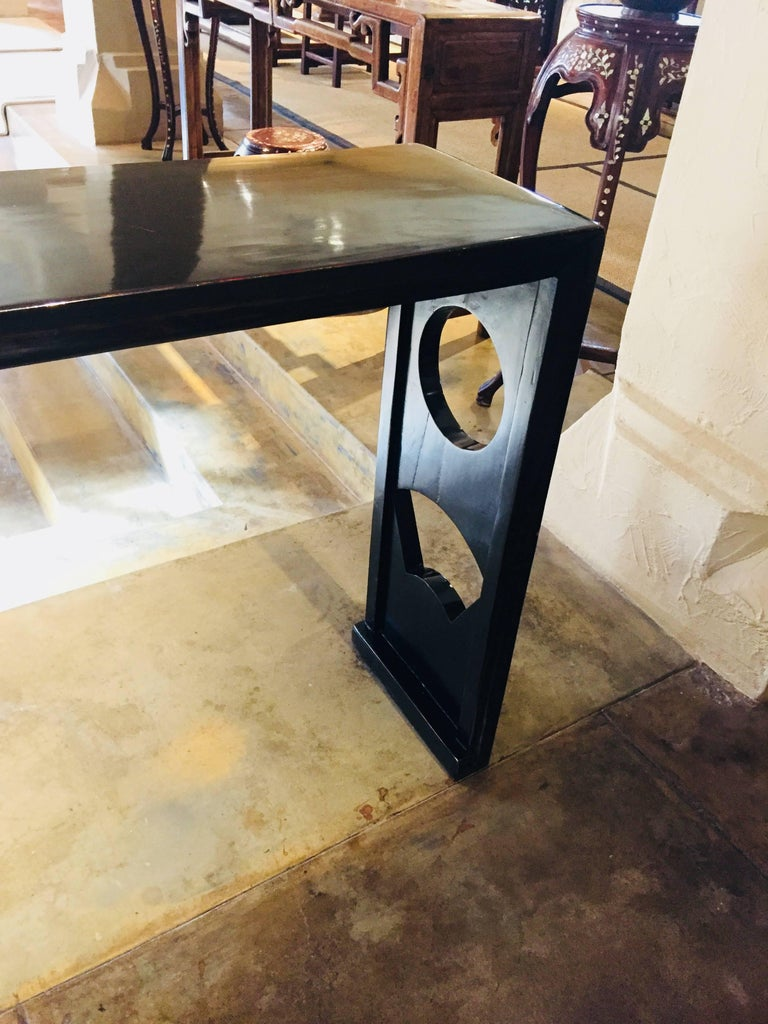 This unique black lacquer wood console table is from China from the Shanxi Province. It is 75 L x 12 D x 33 H  It has a modern look with the cut outs in the legs, circle and a half circle.   The finish is lovely.