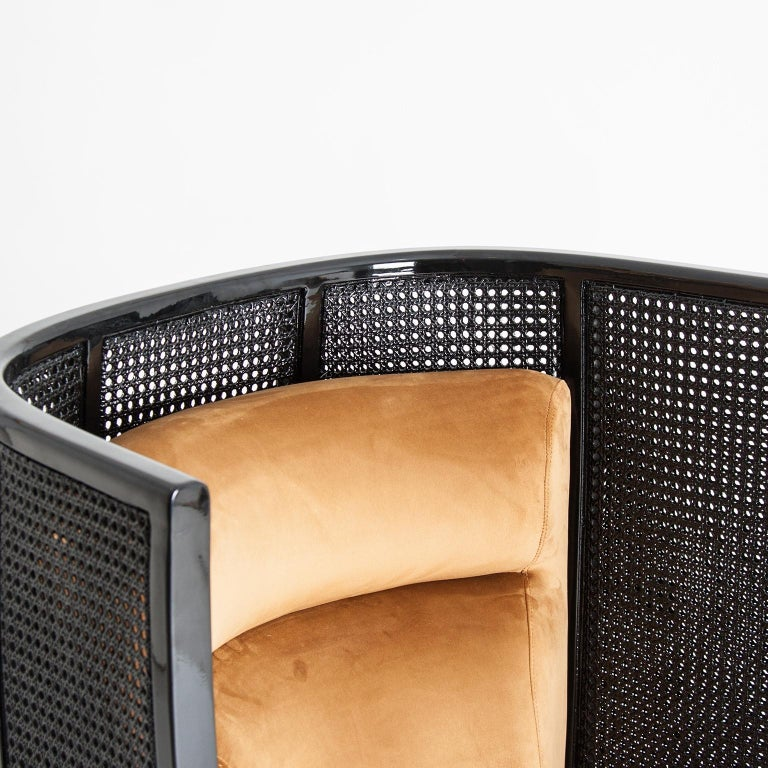 Black lacquered woven wicker cane with gold feet, velvet lounge armchair.