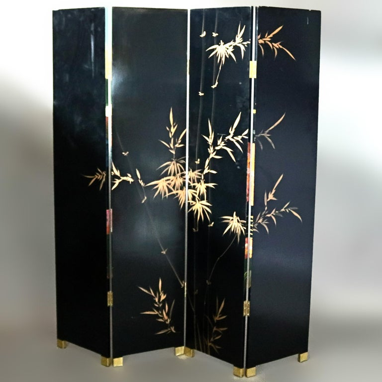 A Chinese dressing screen offers four panels having black lacquered finish, front with more recent Severin Roesen School fruit and foliate still life painting and en verso gilt bamboo painting, raised on brass feet, 20th century  ***DELIVERY NOTICE